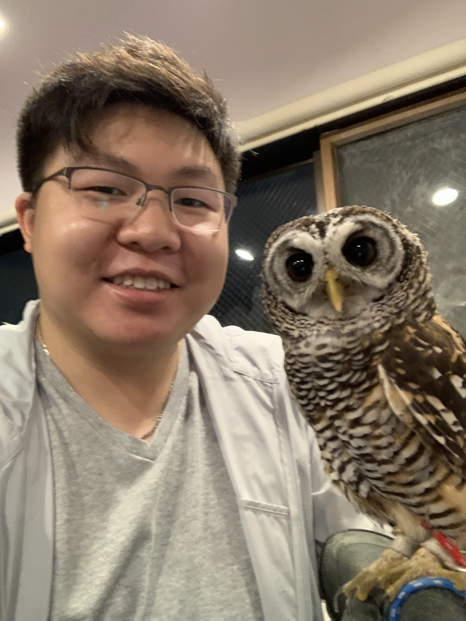 Self-taken photograph of Darrin and an owl standing on his arm